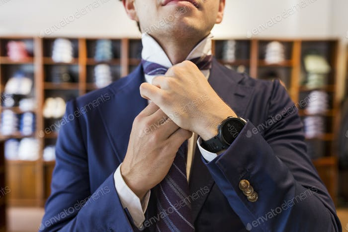 Young man tying tie in clothing store