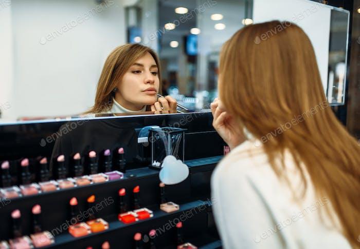 Female client testing lip liner in make-up shop