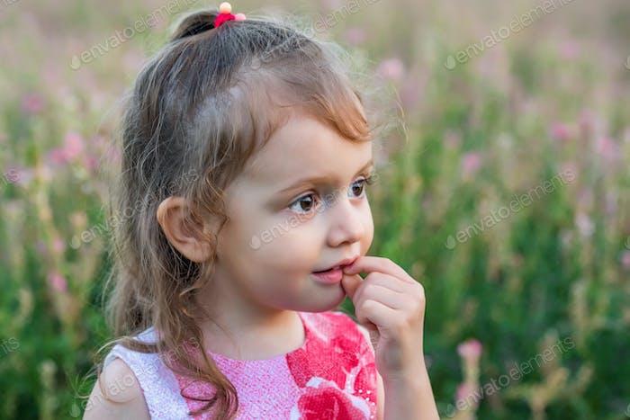 Cute baby girl looks aside outdoors in green field. Child portrait