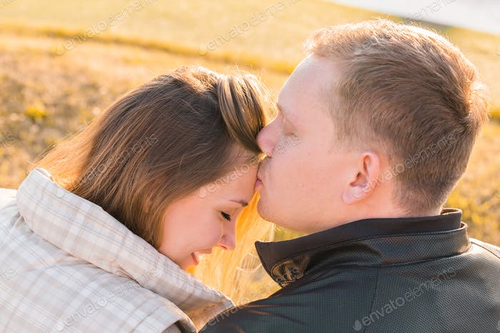 Sweet kiss. Handsome young man kissing his girlfriend on forehead in autumn park