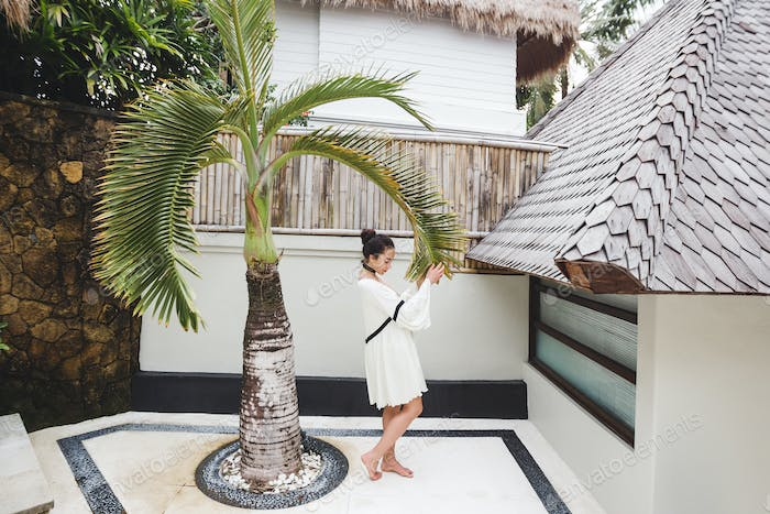 Woman in white tunic in tropical garden with palm tree and white background. Fashion shoot