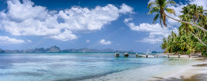 Beautiful tropical beach. Crystal clear lagoon with palms around and impressive white clouds