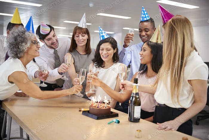 Colleagues celebrating a birthday in the office make a toast