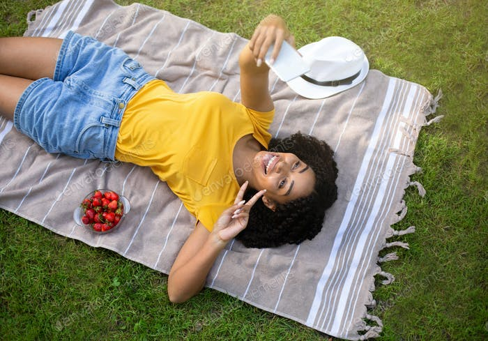 Attractive black girl making silly face while taking selfie on blanket at park, top view
