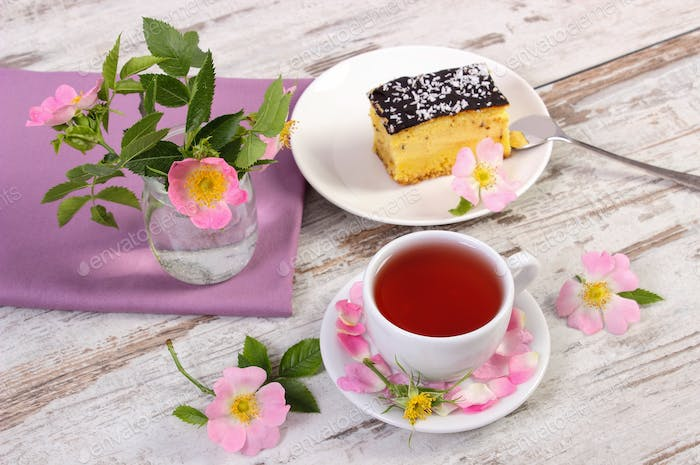 Cup of tea with cheesecake and wild rose flower on rustic board