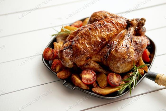 Gebratenes ganzes Huhn in schwarzer Pfanne aus Gusseisen