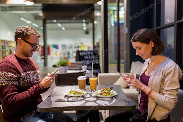 happy couple with smartphones at vegan restaurant