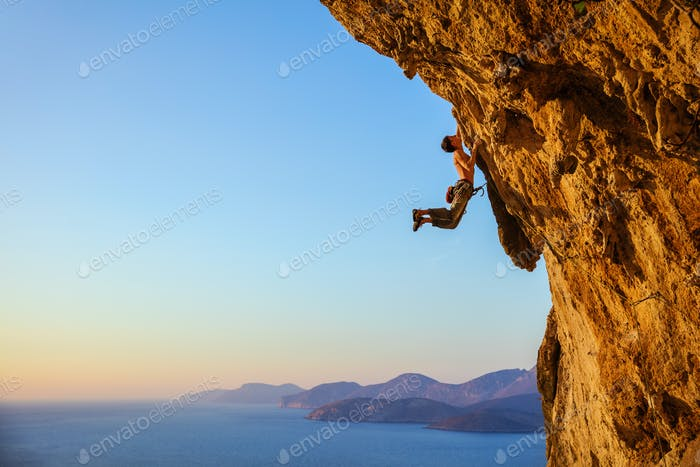 Rock climber jumping on handholds while climbing overhanging clif