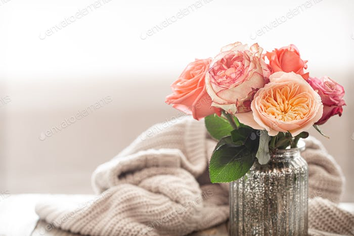 Cozy arrangement with roses on a wooden table