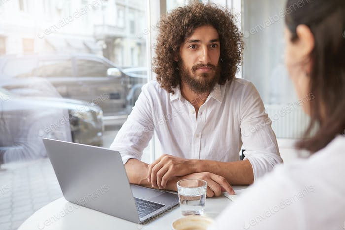 Young good looking bearded businessman having appointment out of office, having pleasant talk
