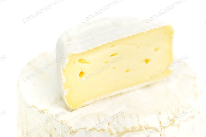 Round camembert cheese with a piece on white background