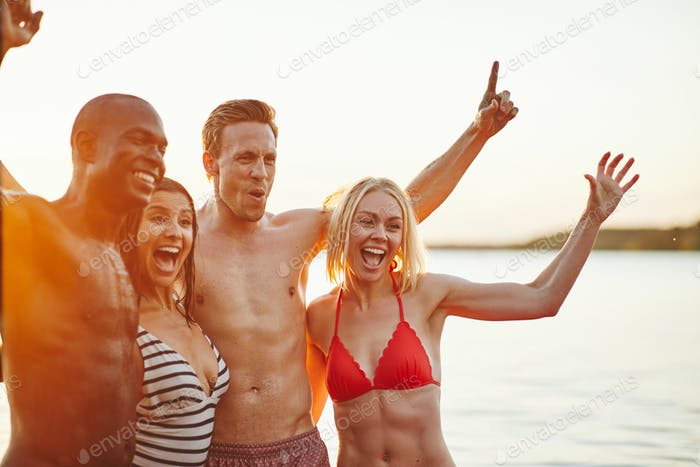 Group of young friends having fun together at a lake