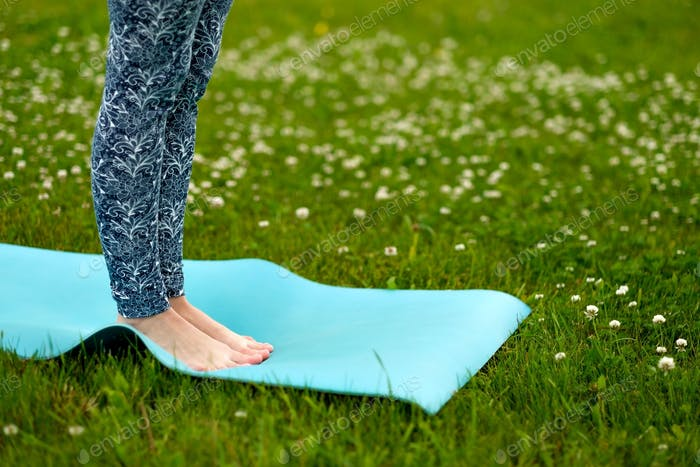Young woman doing yoga exercise on green grass. face is not visible.