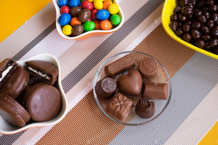 Bowls filled with different kinds of brown and colorful chocolates of different colors and shapes