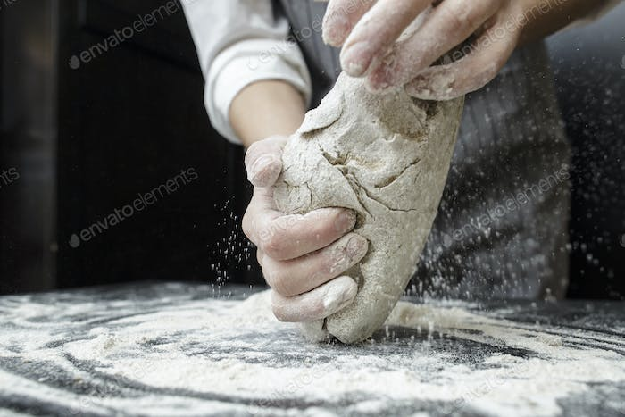 Human hands knead the dough on a black wooden table