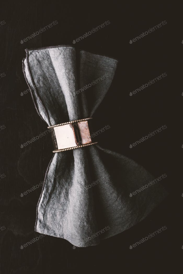 Grey napkin in the vintage metal ring on the black wooden table
