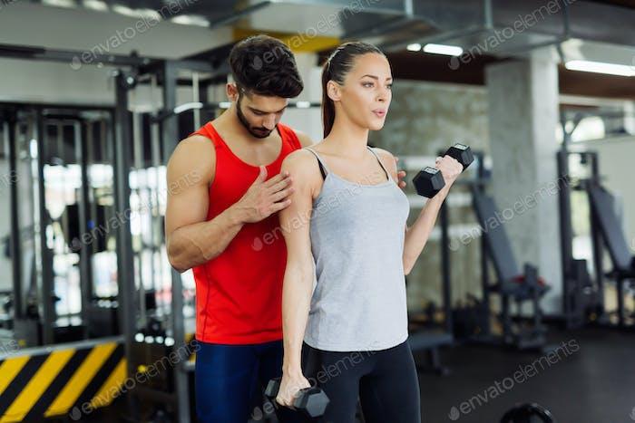 Mujer adulta joven Trabajo fuera en gimnasio con entrenador