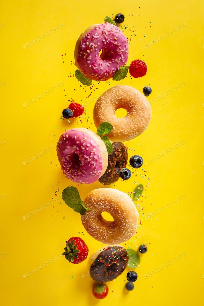Verschiedene dekorierte Donuts mit Streuseln und Beeren in Bewegung fallen auf gelblichen Hintergrund