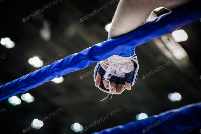 hand of  fighter on ropes of ring