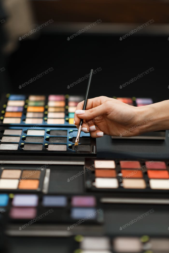 Woman with brush choosing eye shadows in store