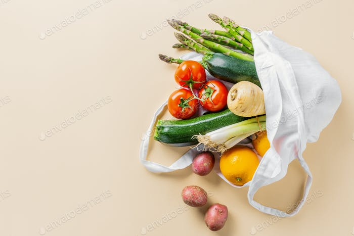 Different vegetables in textile bag on beige