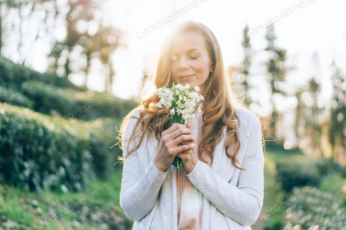 Woman in backlight smelling and showing off her beautiful snowdrops flowers bouquet.