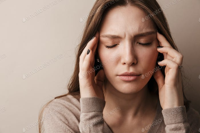 Photo of young beautiful woman with headache rubbing her temples
