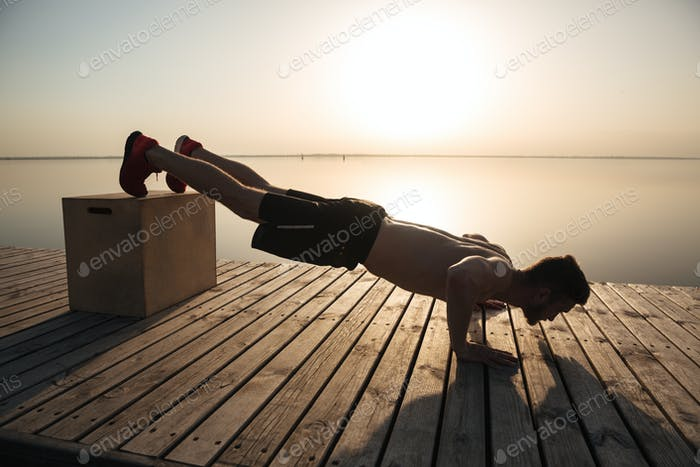 Young healthy man doing push-ups with special equipment