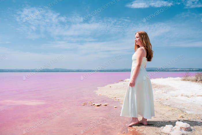 Side view of cute teenager woman wearing summer clothes on pink lake