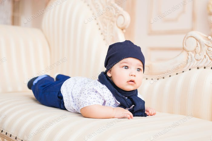 Adorable baby boy in white sunny bedroom. Newborn child.
