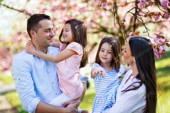 Young parents with small daugthers standing outside in spring nature