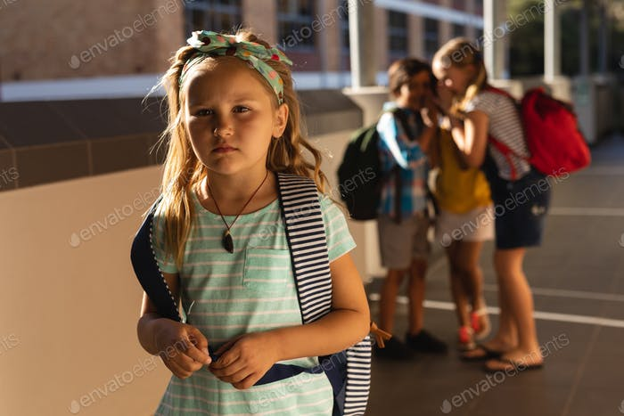 Front view of school friends bullying a sad girl in hallway of elementary school