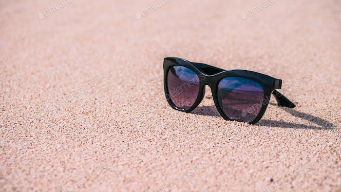 Sonnenbrille am Sandstrand an sonnigen Tag, gespiegelter Ozean und Himmel, Bali
