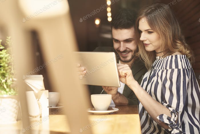 Couple using digital tablet in cafe restaurant