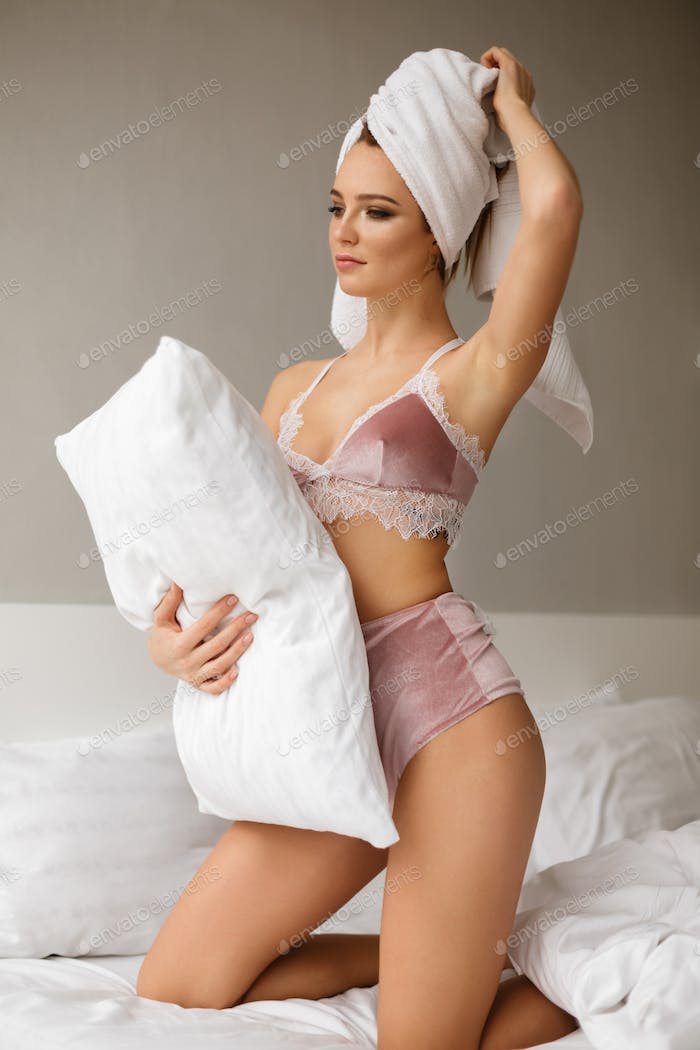 Beautiful lady standing on knees in bed with towel on her head and holding white pillow in hand