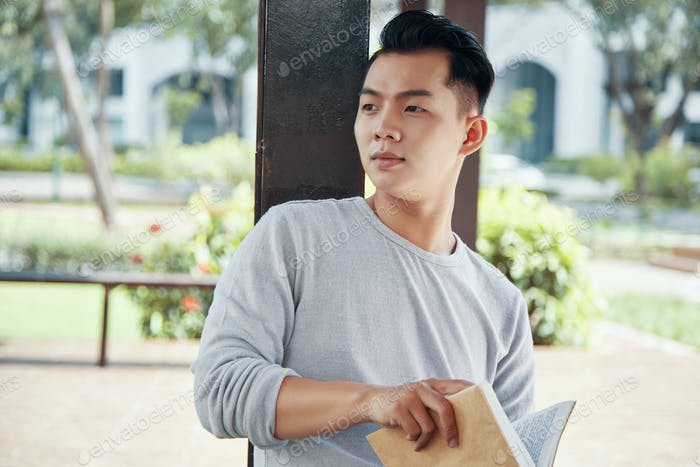 Asian man with book looking away