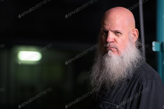 Portrait Of Bald Man With Gray Beard Outdoors At Night