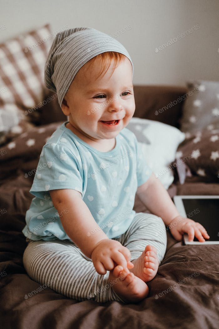 Cute little happy baby girl plays sitting on a bed in a room. Happy family having fun.
