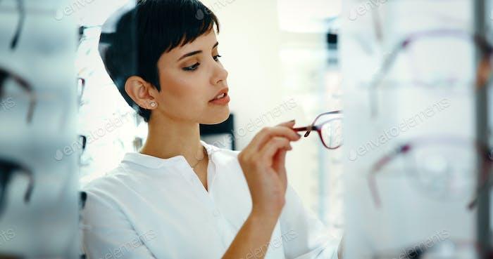 Mujer joven bonita está eligiendo Novedad gafas en la tienda de óptica