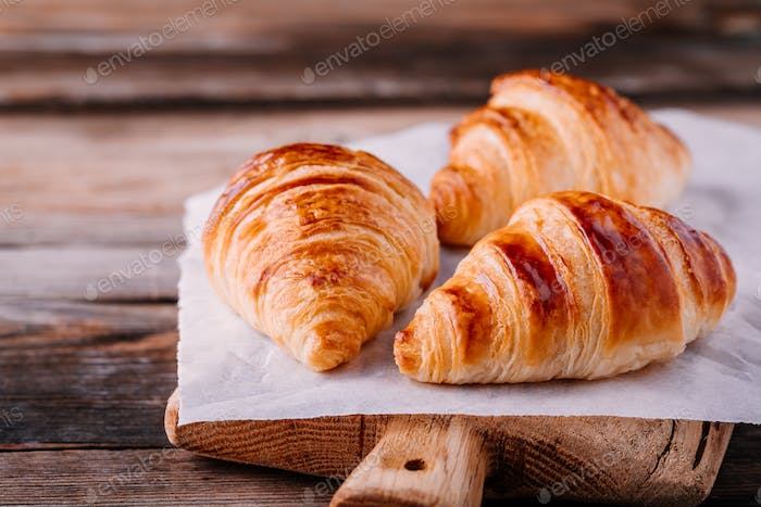 Homemade baked croissants on wooden rustic background