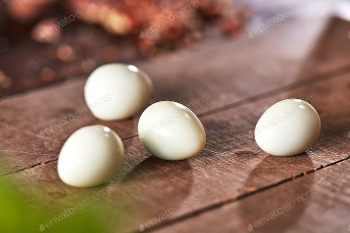Cooking peeled quail eggs presented on an old wooden table. Ingredient for Healthy Salad