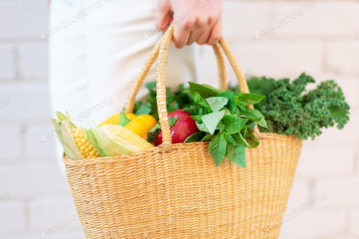 Zero waste concept with copy space. Woman holding straw basket with vegetables, products. Eco