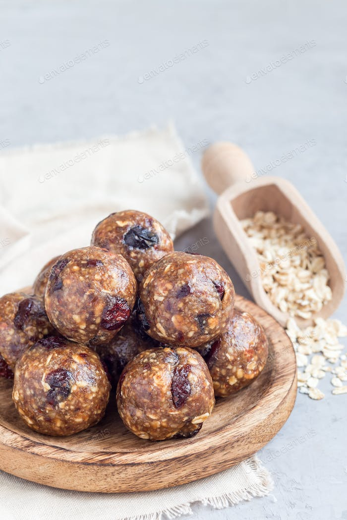 Healthy homemade energy balls with cranberries, nuts, dates and rolled oats, vertical, copy space