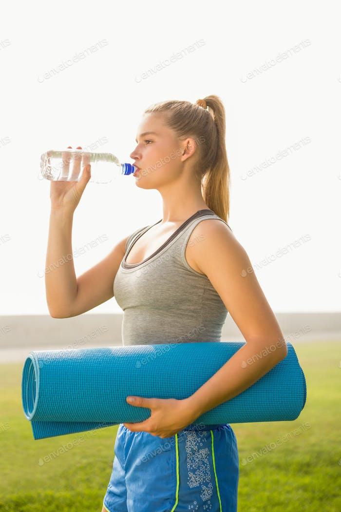 Sporty blonde holding exercise mat and drinking water in parkland