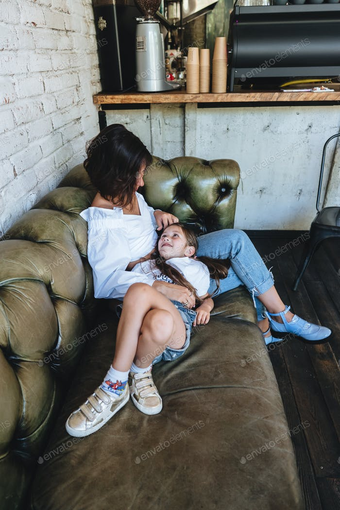 Mom and her little girl have fun on the couch