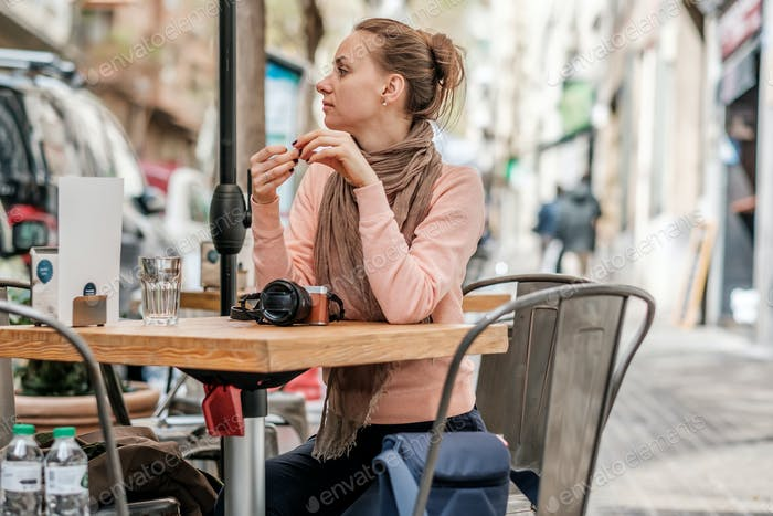 Woman with camera in outdoor cafe. Barcelona, Catalonia.