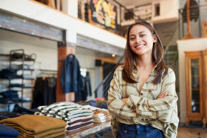 Portrait Of Smiling Female Owner Of Fashion Store Standing In Front Of Clothing Display