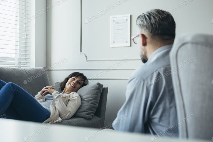 Happy housewife lies on the grey couch in front of counselor