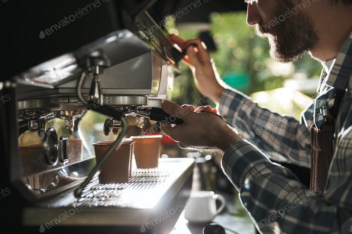 Image closeup of attractive barista man making coffee while work