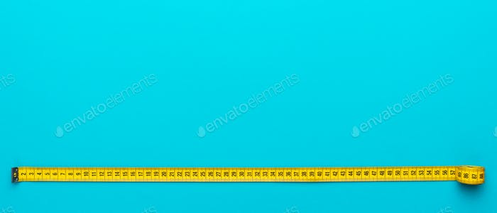 Top View Of Yellow Measuring Tape Over Turquoise Blue Background With Copy Space